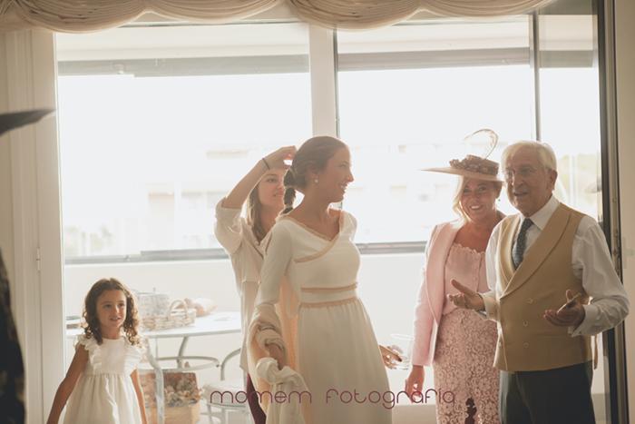 contraluz novia y familia de pie peinándola-Boda de campo