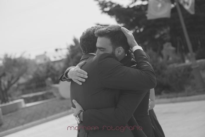 abrazo novio y amigo en puerta iglesia-Boda de campo