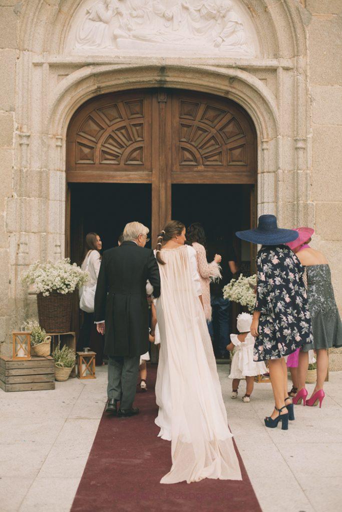 entrada novia de espaldas puerta iglesia al fondo-Boda de campo