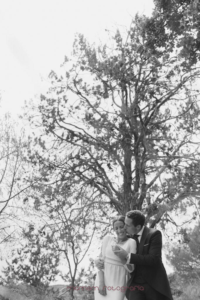 novios agarrados árbol detrás-Boda de campo
