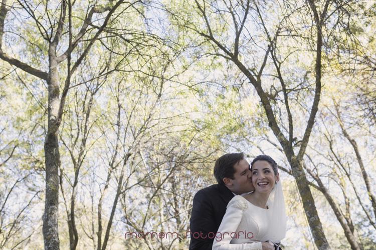 novio abraza y besa a la novia con árboles detrás-fotografías de boda