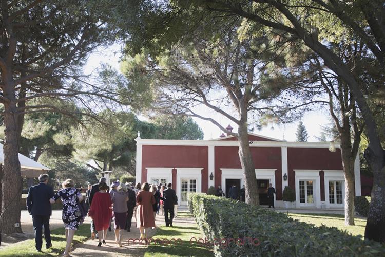 invitados en el jardín se dirigen a la zona de mesas-fotografías de boda