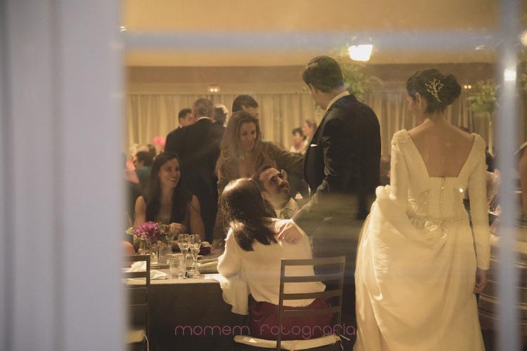 novios con invitados en interior a través de cristal-fotografías de boda