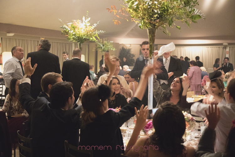invitados en la mesa alzando manos-fotografías de boda