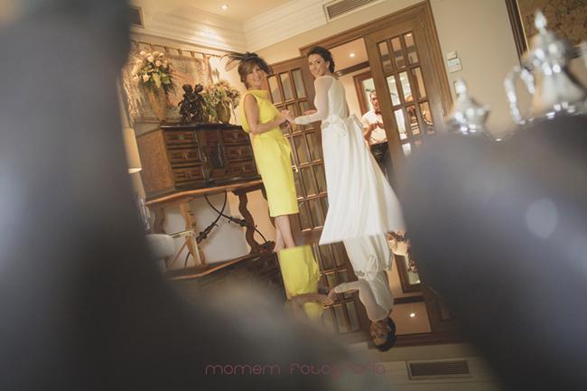 Novia y su madre cogidas de las manos mirando hacia cámara por detrás-Fotografías de boda
