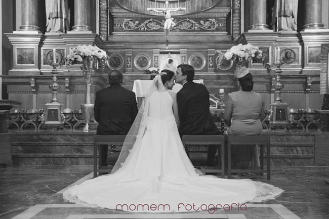 vista altar de espaldas novio besa frente de novia-Fotografías de boda