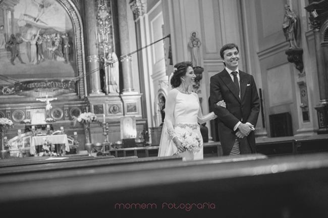 novios saliendo con bancos en primer plano-Fotografías de boda
