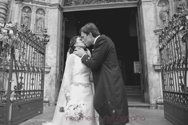 novios besándose puerta rejas iglesia detrás-Fotografías de boda