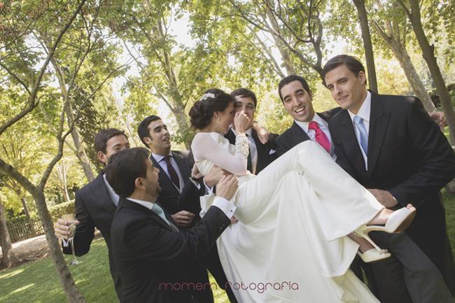 novios amigos que cogen en brazos a novia que se tapa la cara-Fotografías de boda