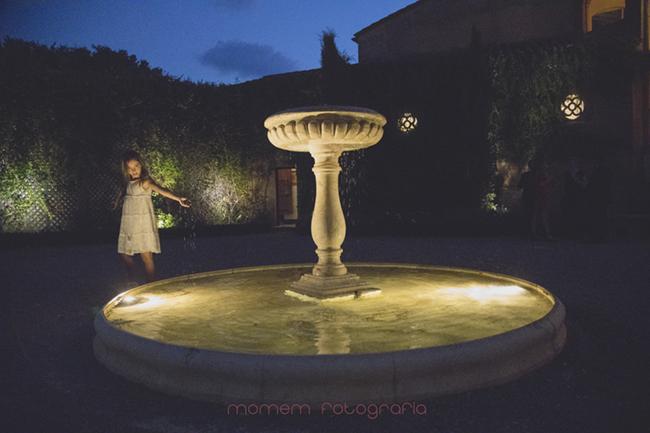 niña jugando de noche en fuente exterior iluminada-Fotografías de boda
