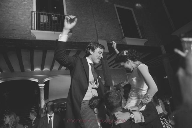 novios cogidos en brazos por invitados bailando-Fotografías de boda