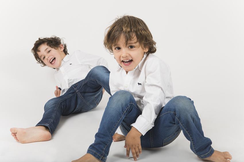 hermanos jugando sobre fondo blanco de Momem Fotografia