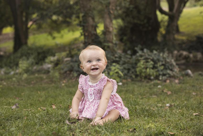 niña sobre cesped sonriendo de Momem Fotografia