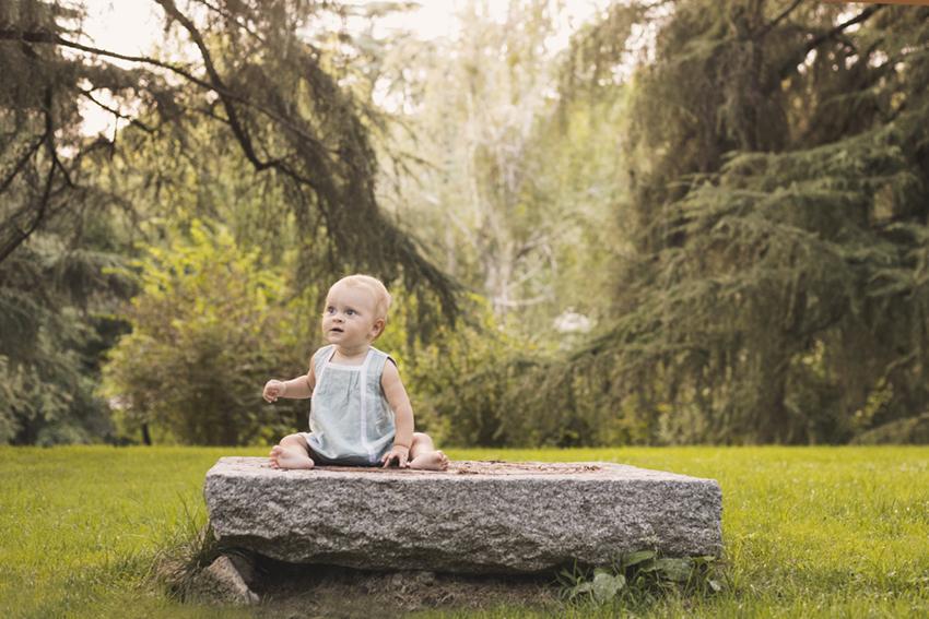 Bebe sentada en piedra en jardin de Momem Fotografia
