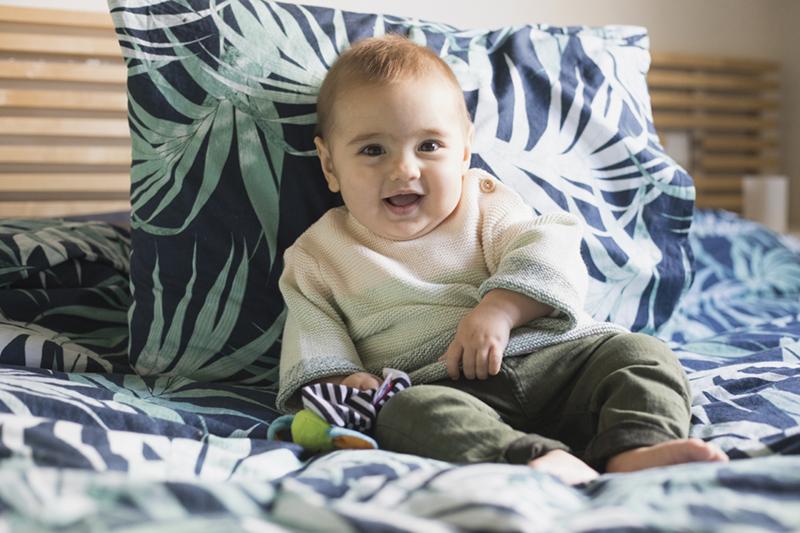 niño sentado en la cama riendo de Momem Fotografia
